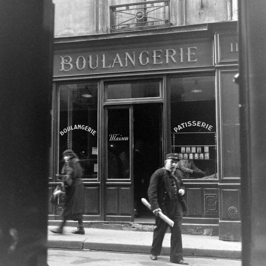 'Cop and Bread in front of a bakery, rue de la Huchette, Paris' by David E. Scherman (American photojournalist and editor, 1916-1997), january 1947