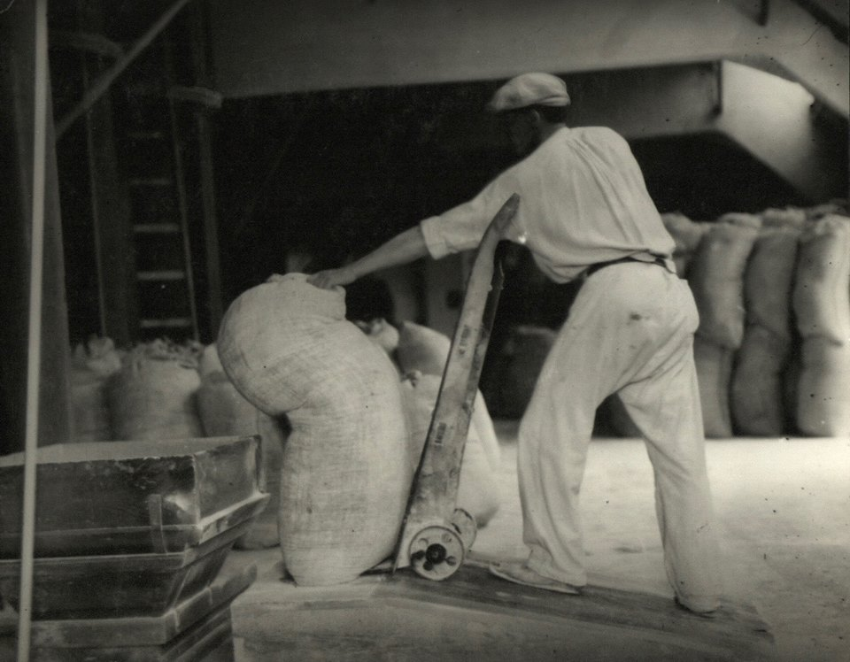 'A worker stacks bag of wheat flour probably at Spillers Mills, United Kingdom' © Mansell Collection, London